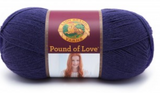 A ball of Lion Brand Pound of Love yarn on white background in shade navy