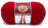 A ball of Lion Brand Pound of Love yarn on white background in shade cherry (bright red)