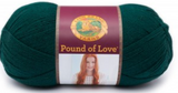 A ball of Lion Brand Pound of Love yarn on white background in shade hunter green