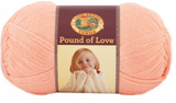 A ball of Lion Brand Pound of Love yarn on white background in shade creamsicle (pale orange/pink)