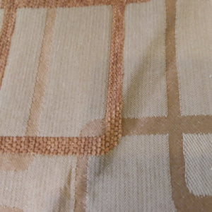 Woven jacquard upholstery fabric in beige with the outlines of overlapping rounded rectangles in tan and gold.
