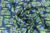 "Swirled swatch licensed Star Wars (The Child) printed fabric in Child Cut Out Logo (blue/green ""Star Wars"" text and baby yoda heads on blue)"
