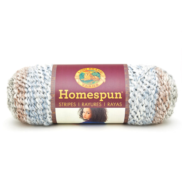 A ball of Lion Brand Homespun in a boucle texture and colourway Beachside Stripes (pale blue, white, sandy brown, light grey)