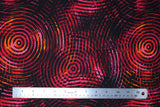 Flat swatch red/pink fabric (black fabric with large groups of concentric circles in shades of red, pink, yellow and orange allover)
