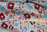 Raw hem swatch docs gadgets fabric (off white fabric with tossed full colour medical emblems: red first aid kits, black x-rays, white charts, coloured pills, blue stethoscopes, etc.)
