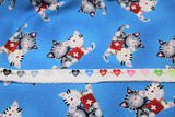 Raw hem swatch comfort kitties fabric (bright medium blue fabric with tossed cartoon grey and white snuggly kitties with red first aid kits)