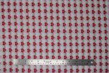 Flat swatch heartbeat fabric (grey fabric with alternating stripes of red hearts with red/white beat lines, and faint white hearts with beat lines)