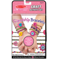 Grab and Go Craft Activity Set: Friendship Bracelets.  Two youth hands with interlaced fingers, each wrist wearing a variety of different friendship bracelet styles.  More bracelets are laid out in horizontal stripes behind the hands.