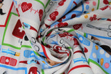 Swirled swatch happy helpers fabric (white fabric with cartoon dogs and cats with medical equipment in primary coloured frames, various medical emblems in full colour: scissors, syringe, red hearts with beat lines, pills, bottles, etc.)