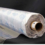 A partly unfurled roll of clear soft vinyl with white backing paper covered in blue motifs.  The end of the roll has a label with a 4 on it.