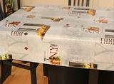 "NY Taxi (scattered phrasing such as ""N.Y."" and ""TAXI"" in red, light grey, and taupe print scattered with New York scenes, yellow taxis, and traffic lights, all on an off-white background) opaque vinyl draped over a dining room table with matching chairs around it."