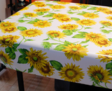 Sunflowers (bright, large sunflowers with a few leaves over a bright white background) opaque vinyl draped over a dining room table with matching chairs around it.