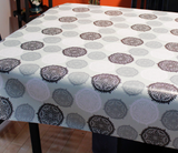 Black Oval (stylized circular motifs with a central pointy flower design repeated in black, grey, and white on a pale green background) opaque vinyl draped over a dining room table with matching chairs around it.