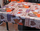 Wildlife (deer and foxes scattered among orange maple leaves, wrought iron decorative elements, bark textured hearts, and other rustic decor motifs, over off-white background) opaque vinyl draped over a dining room table with matching chairs around it.
