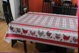 Chickens (a central pattern of white, red, and grey plaid, with a border on either side of the width of a thick red line, red and grey plaid, a white field with solid red and grey chickens and red and grey plaid chickens Then another solid band of red and a band of red and grey up to the edge) opaque vinyl draped over a dining room table with matching chairs around it.