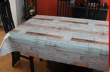Rustic Wood (weathered boards from off-white to dark tan in offset rows running parallel to the natural edge) opaque vinyl draped over a dining room table with matching chairs around it.