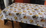 Coffee (scattered yellow mugs filled with brown liquid, yellow cup and saucer sets, black basket with yellow trim, and clusters of coffee beans on a white background) opaque vinyl draped over a dining room table with matching chairs around it.