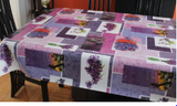Lavender (lavender, indigo and mauve printed rectangles overlap each other along with white rectangles featuring pictures of lavender sprigs, baskets of lavender, or lavender fields) opaque vinyl draped over a dining room table with matching chairs around it.