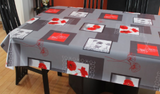 Grey w/poppies (white blocks with red poppies and dark grey borders are scattered among dark grey rectangles and red rectangles with line drawings of poppies in white or red over top, all on a mid grey background) opaque vinyl draped over a dining room table with matching chairs around it.