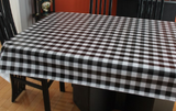 Black and White Check (black and white gingham pattern with black bands over a white background) opaque vinyl draped over a dining room table with matching chairs around it.