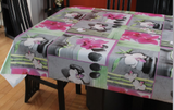 Orchids (white orchids with green leaves, dark grey smooth stones, bamboo shots and bright pink accents are arranged on grey, white and watercolour green backgrounds, arranged loosely in overlapping square motifs) opaque vinyl draped over a dining room table with matching chairs around it.