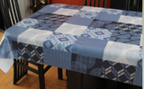 Blue decor (squares of blue geometric elements such as chevrons and overlapping circles in shades of navy, mid blue, pastel blue and white) opaque vinyl draped over a dining room table with matching chairs around it.