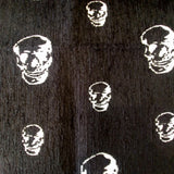 Jacquard upholstery fabric with stylized white skulls of varying sizes scattered on a black background