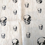 Jacquard upholstery fabric with stylized black skulls of varying sizes scattered on a white background
