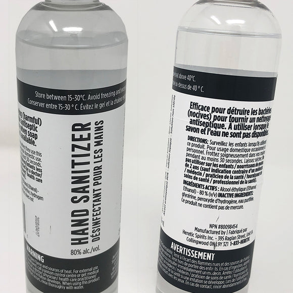 Two tall, slender plastic bottles stand side by side, photographed from the neck down to the bottom of the label. The bottle is almost full of a clear liquid. The two bottles have different angles of the label, printed in both English and French. In a top black band with white text,