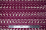 Flat swatch burgundy winter pattern fabric (Burgundy fabric with white Christmas sweater style pattern stripes with pixelated triangle design and quilt like floral repeated)