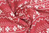 Swirled swatch red winter pattern fabric (red fabric with white Christmas sweater style pattern stripes with pixelated triangle design and quilt like floral repeated)
