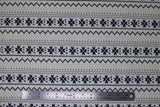 Flat swatch white winter pattern fabric (white fabric with black/navy Christmas sweater style pattern stripes with pixelated triangle design and quilt like floral repeated)