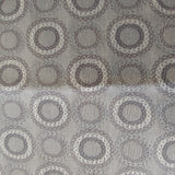Square swatch upholstery fabric with circles (within circles) print in neutral/grey/beige shades