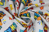 Swirled swatch Paw Patrol print in Rubble, Marshall and Chase (light grey fabric with character dogs and names tossed allover with white bones, yellow arrows, orange and blue stars)