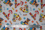Flat swatch Paw Patrol print in Rubble, Marshall and Chase (light grey fabric with character dogs and names tossed allover with white bones, yellow arrows, orange and blue stars)
