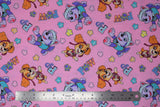 "Flat swatch Paw Patrol print in Sky and Everett (light pink fabric with character dogs and ""PP"" ""POW"" tossed text and multi coloured paw prints)"