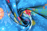Swirled swatch medium blue fabric with shadow floral and colourful flowers and giraffes, butterflies, high heeled shoes, printed fabric