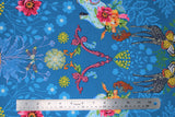 Flat swatch medium blue fabric with shadow floral and colourful flowers and giraffes, butterflies, high heeled shoes, printed fabric