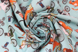 Swirled swatch cat themed fabric in bike race (light blue turquoise coloured fabric with assorted cartoon cats on regular and tandem bikes)