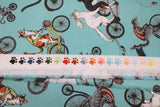 Raw hem swatch cat themed fabric in bike race (light blue turquoise coloured fabric with assorted cartoon cats on regular and tandem bikes)