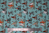 Flat swatch cat themed fabric in bike race (light blue turquoise coloured fabric with assorted cartoon cats on regular and tandem bikes)