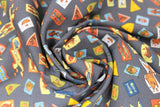 Swirled swatch cat themed fabric in pennants (charcoal grey coloured fabric with multi-coloured assorted size and shape cat related badges tossed allover)