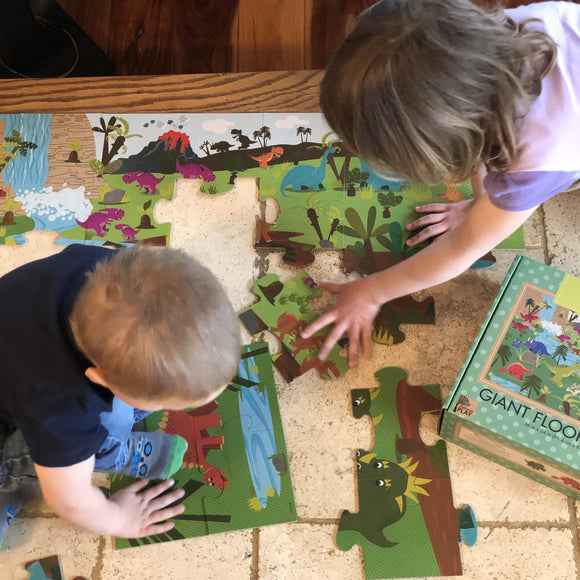 Two children playing on floor with giant floor puzzle pieces