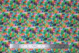 Flat swatch Borabora fabric (white fabric with heavily layered tropical style leaves in black, green, blue, pink, orange ranging in levels of transparency)