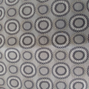 Square swatch upholstery fabric with circles (within circles) print in silver/black/grey shades