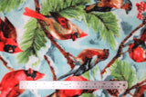Flat swatch spruce cardinal fabric (light blue/white sky look fabric with green and brown spruce tree branches holding red cardinals, red berries, and pinecones)