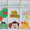 An assortment of packages of appliques, including frogs and fishes, little monkeys, and yellow ducks