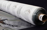 A partly unfurled roll of clear soft vinyl with white backing paper covered in black motifs. The end of the roll has a label with a 10 on it.