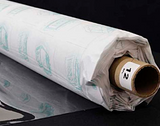 A partly unfurled roll of clear soft vinyl with white backing paper covered in green motifs. The end of the roll has a label with a 12 on it.