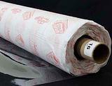 A partly unfurled roll of clear soft vinyl with white backing paper covered in red motifs. The end of the roll has a label with a 16 on it.